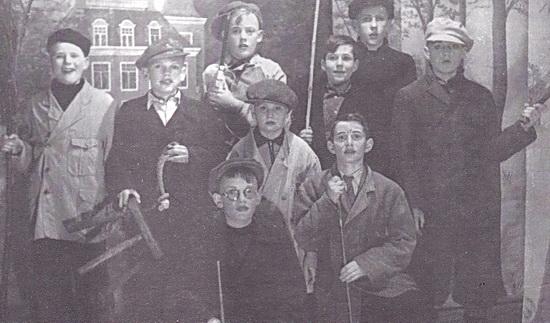 Foto toneelluk O.L.S. Midwolda 1953 met tweede van links, met pet en melkkrukje: Hemmo Blaauw