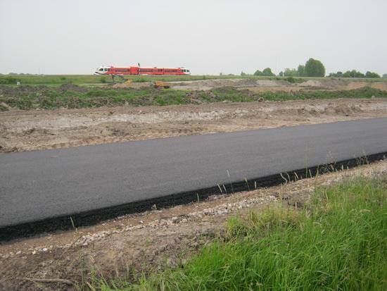 De nieuwe weg met een dikke laag asfalt! Op de achtergrond, op de oude spoorbaan, de Arrivatrein tussen Groningen en Leeuwarden... Of: tussen Zuidhorn en Grijpskerk....