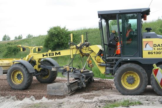 Een van de vele ingenieuze machines die ingeschakeld zijn om hier vlot een nieuwe weg aan te leggen. En dat lukt!