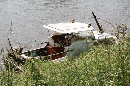 Hé, bij de huizenkant van het Van Starkenborghkanaal een onbeheerd achtergelaten motorboot(je), nauwelijks te zien achter het hoge bermgras. Mooi bootje!
